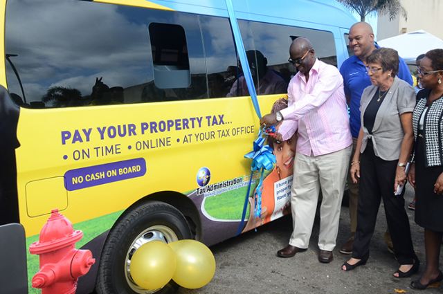Local Government and Community Development Minister, Hon. Desmond McKenzie (left), cuts the ribbon to officially launch the mobile property tax unit in Port Maria, St. Mary, on February 8. Others (from second left) are: Mayor of Port Maria, Councillor Richard Creary; President of the Lay Magistrates Association in St. Mary, Maxine Marsh; and Parish Manager, Tax Administration Jamaica (TAJ), St. Mary, Cynthia Gilmore.
