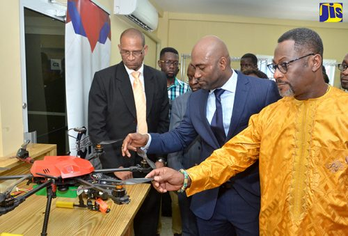 Minister of Science, Energy and Technology, Dr. the Hon. Andrew Wheatley (second right), examines his new drone which was made in the Dr Andrew Wheatley Centre for Digital Innovation & Advanced Manufacturing and presented to him as a gift on Wednesday, November 15. Occasion was the official opening of the facility. At right is the Chancellor, Caribbean Maritime University, His Royal Majesty Drolor Bosso Adamtey I.