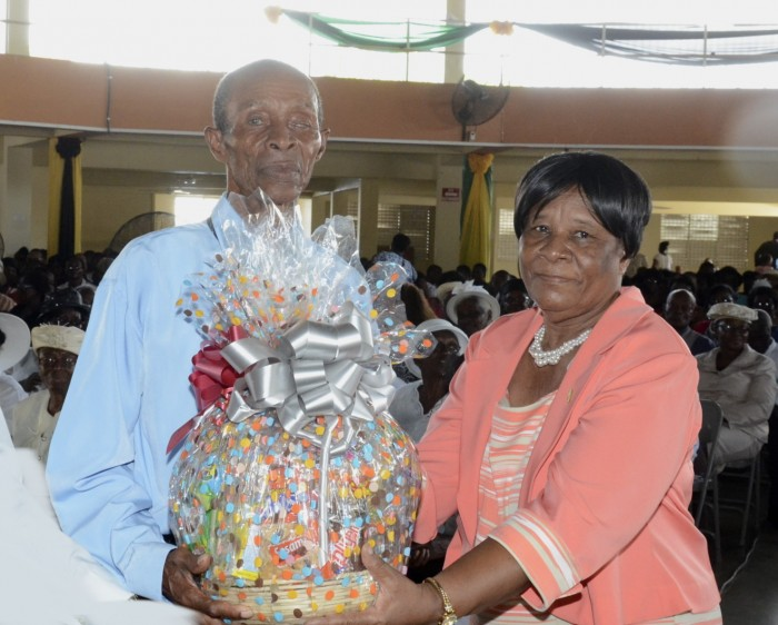 Eighty-eight year old Joshua Richards is presented with a gift basket by Committee Member of the Caribbean Community of Retired Persons, Beverly Hall-Taylor, during the National Senior Citizens' Week church service held yesterday (September 27), at the Church of God of Prophecy, Old Harbour Road, St. Catherine. The day was also observed as National Grandparents Day.
