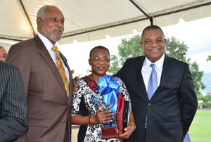 The 2013 Civil Servant of the Year, Miss Enthrose Campbell (centre), who is also Director of Production at the Jamaica Information Service (JIS), is flanked by Minister with Responsibility for the Public Sector, Hon. Horace Dalley (right), and Cabinet Secretary, Ambassador Douglas Saunders (right), at the 2013 Jamaica Civil Service Long Service Awards ceremony, held at King's House in Kingston, on November 20.