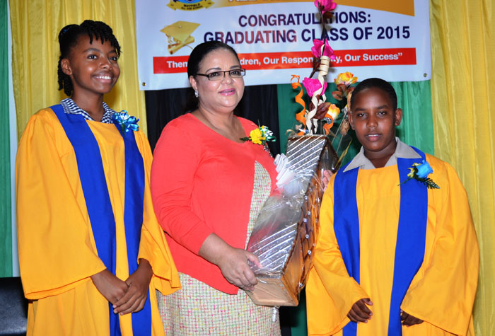 Information Minister, Senator the Hon. Sandrea Falconer (centre), is flanked by students of the Mayfield All Age School, in St. Elizabeth, Ashley Wellington (left) and Demitri Juggi, after they presented her with a gift for having being the guest speaker at their graduation ceremony, held on July 2 at the St. Mark Anglican Church Hall, in Southfield, St. Elizabeth. The Minister is also a past  student of the school.