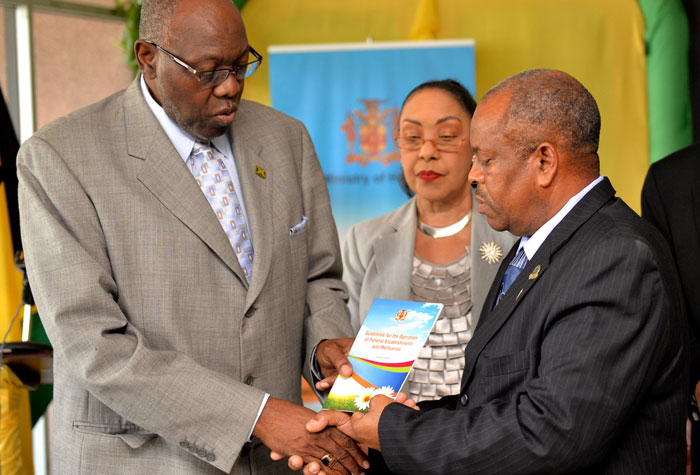 Minister of Health, Hon. Dr. Fenton Ferguson (left), hands over guidelines for the operation of funeral establishments, and mortuaries, to President of the  Funeral Directors' Association, Melvin Honeyghan (right), at his Downtown Kingston offices, on October 21. Looking on is Chief Medical Officer, Dr. Marion Bullock DuCasse.