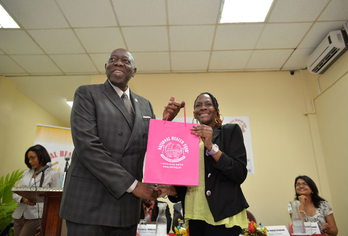 Minister of Health, Hon. Dr. Fenton Ferguson (left), presents a National Health Fund (NHF) card to sickle cell patient, Keino Ward (right). Occasion was a ceremony to formally announce the addition of Sickle Cell Disease (SCD) to the NHF Individual Benefits programme, held on Tuesday (June 30), at the New Kingston Conference Centre.
