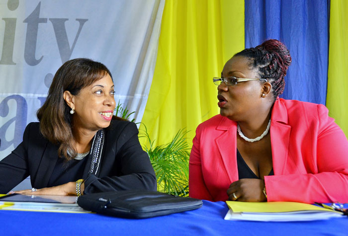 Minister of State in the Ministry of Industry, Investment and Commerce, Hon. Sharon Ffolkes Abrahams (left), converses with Dean of the Faculty of Business, Management and Law at the International University of the Caribbean (IUC), Kerry-Ann Metcalfe-Green. Occasion was leadership conference, held today (July 1), at the university's  campus on Old Hope Road, St. Andrew.