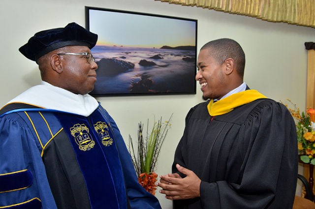 State Minister in the Ministry of Education, Youth and Information, Hon. Floyd Green (right) is in light conversation with President of the Northern Caribbean University (NCU), Dr. Lincoln Edwards (left), just before the start of the Honours Convocation ceremony on the grounds of the institution in Mandeville, Manchester, on October 19.