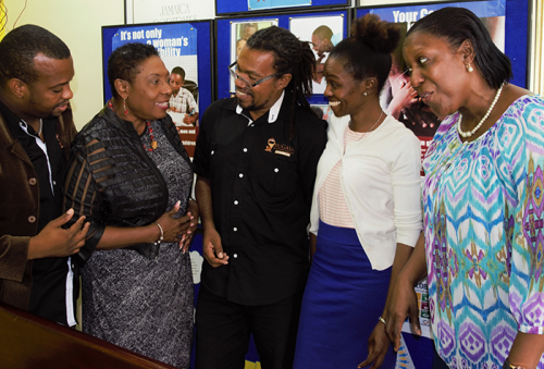 Minister of Culture, Gender, Entertainment and Sport, the Honourable Olivia Grange, shares the details of her favourite scene from the 'Amazing Dads' mini-series with Rev. Jayson Downer, President, Men of God Against Violence and Abuse (MoGAVA); Rev. Courtney Morrison, Chairman, MoGAVA; Takesha Sten-Barnes, Aids Healthcare Foundation and Sharon Coburn Robinson, Director, Policy and Research, Bureau of Gender Affairs (l-r). The Amazing Dad mini-series, developed by MoGAVA was launched today (October 20) at the Management Institute for National Development in Kingston. The series will highlight the positive role of men, specifically fathers. It will demonstrate how fathers can be actively involved in the growth and development of their child/children amidst the challenges.