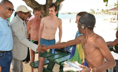 Minister of Tourism, Hon. Edmund Bartlett (second left) greets visitors during a tour of the Ocho Rios Bay Beach, in St. Ann on May 20. At Left is Executive Director of the Tourism Product Development Company, Dennis Hickey.