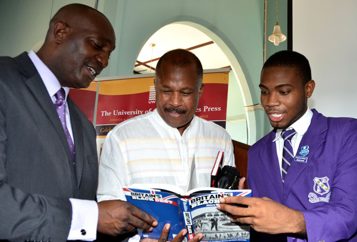 Chairman of the CARICOM Reparation Commission, Professor Hilary Beckles (centre), along with Principal, Kingston College, Dave Myrie (left) and Kingston College Head Boy, Chevon Lewis, peruse a copy of his book, 'Britain's Black Debt', following a lecture on reparation justice at the school on April 15.