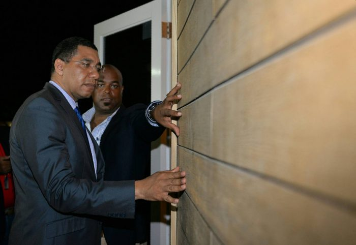 Prime Minister, the Most Hon. Andrew Holness (left), inspects the exterior of the 'tiny house' which was on display at the opening of the three-day Build Expo and Conference at the Montego Bay Convention Centre in St. James on June 9. At right, Conference Chairman, Dwight Crawford, highlights the features.