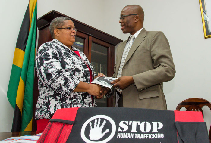 Permanent Secretary, Ministry of Justice, and Chairperson, National Taskforce Against Trafficking in Persons (NATFATIP), Mrs. Carol Palmer officially hands over surveillance equipment to Head of the Organised Crime Investigation Division (OCID), Senior Superintendent of Police (SSP), Clifford Chambers, on February 26, at the Ministry, in Kingston. The surveillance equipment is expected to improve the intelligence gathering process and the quality of evidence in undercover operations.