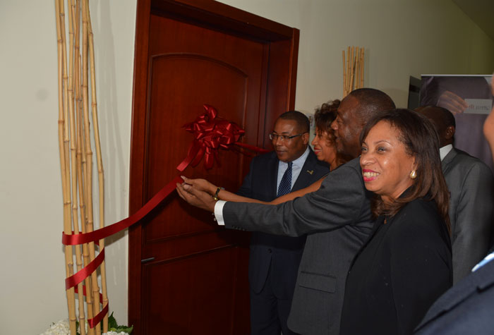 Minister of Industry, Investment and Commerce, Hon. Anthony Hylton (left), assisted by President of JAMPRO, Diane Edwards (second left) and Mayor of Montego Bay and Chairman of the St. James Parish Council, Councillor Glendon Harris, as he cuts the ribbon to signal the official opening of the new JAMPRO regional Office at the Montego Bay Convention Centre in Rose Hall, St. James, on July 24.  At right is Minister of State in the Ministry of Industry, Investment and Commerce, Hon.Sharon Ffolkes Abrahams.