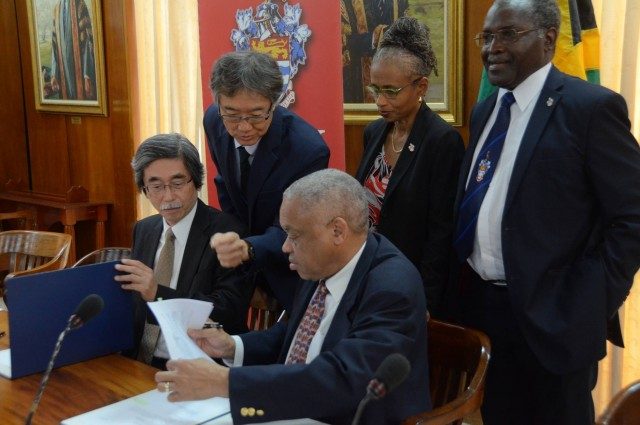 Pro Vice Chancellor and Principal of the University of the West Indies (UWI), Mona, Professor Archibald McDonald (seated, right), along with Ambassador of Japan to Jamaica, His Excellency Mr. Masanori Nakano (seated, left), sign a contract for grant funding, valued at US$90,000, being provided by the Japanese government to UWI for the construction of a gymnasium to facilitate gymnastic training at the institution. Looking on are (from left): Japanese Deputy Chief of Mission to Jamaica, Mr. Hiromoto Oyama; Campus Registrar, Mrs. Camille Bell-Hutchinson; and Deputy Principal, Professor Ishenkumba Kahwa. The signing ceremony was hosted at the UWI Council Room on Wednesday, March 2.