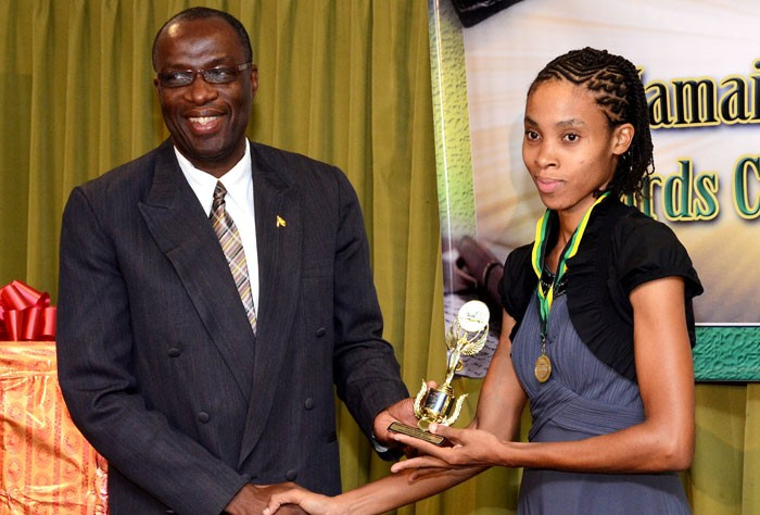 Executive Director of the Jamaica Cultural Development Commission (JCDC), Delroy Gordon  (left) presents a trophy to Best Junior Poet in the JCDC 2013 Jamaica Creative Writing Competition, Ava-gay Bennett.