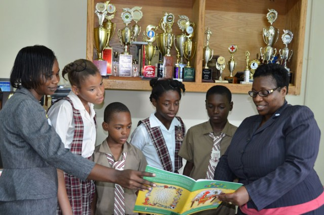Principal of the St. James-based John Rollins Success Primary School, Yvonne Miller-Wisdom (right), along with teacher and Coordinator of the Reading Marathon, Verena Wellington (left), point out features in a reading book to students (from 2nd left): Anya Bernard, Patroy Vernon, Toniann Cowan, and Sebert Walker.