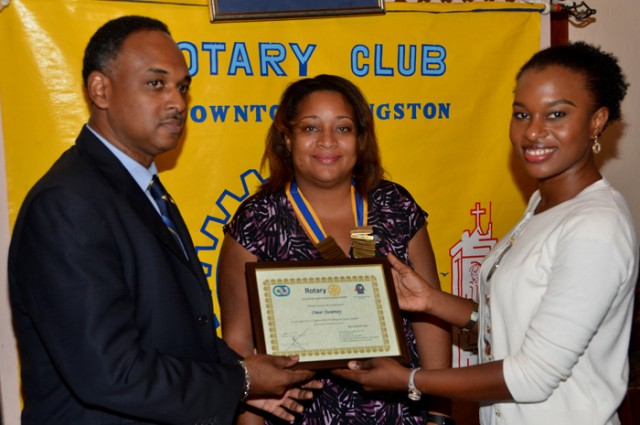 Managing Director of the Jamaica Social Investment Fund (JSIF), Mr. Omar Sweeney (left), accepts a certificate of appreciation from a member of the Rotary Club of Downtown Kingston, Ms. Kahmile Reid (right), following his presentation at a meeting of the Club on Wednesday, February 3, at the Hotel Four Seasons. President of the Club, Ms. Melanie Reece (centre), shares in the moment.