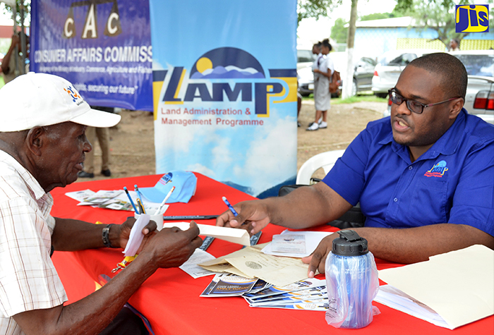 Resident of East Kingston, Adolphus Kelly (left), receives information from Legal Officer, Land Administration And Management Programme (LAMP), Tirshatha Russell. Occasion was the Legal Aid Council's (LAC) fourth justice fair held at the Vauxhall High School on Windward Road, East Kingston, on December 7.