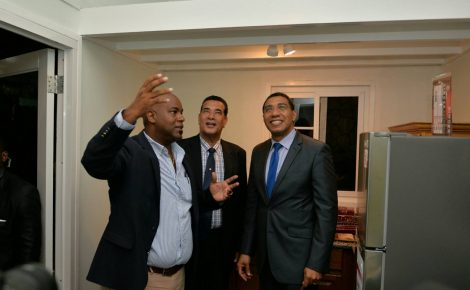 Prime Minister, the Most Hon. Andrew Holness (right); and Mayor of Montego Bay, His Worship Homer Davis, are impressed with the technology that when into the creation of the 'tiny house', which was on display at the opening of the Build Expo and Conference 2017 at the Montego Bay Convention Centre in St. James on June 9. At left, Chairman of the conference, Dwight Crawford, highlights the features.