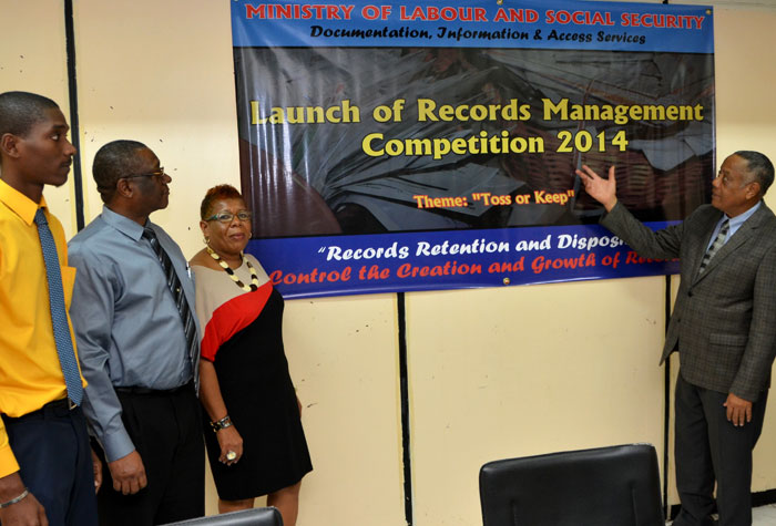 Minister of Labour and Social Security, Hon. Derrick Kellier (right), launches the Documentation, Information and Access Services Unit (DIAS) Records Management Competition 2014, during a ceremony at the Ministry's North Street offices on December 18. Also sharing in the moment are (from left): Registrar, Documentation, Information and Access Services Unit (DIAS), in the Ministry, Winston Walker; Chief Technical Director, Ministry, Errol Miller; and Records Manager, University of the West Indies, Sonia Black.