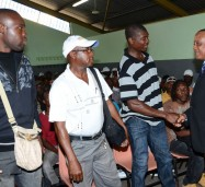 Minister of Labour and Social Security, Hon. Derrick Kellier (right), addressing the first batch of farm workers to be dispatched for 2013 to Canada, under the Ministry's Overseas Employment Programme, on January 2, at East Street in Kingston. The 172 workers will leave the island on January 3, 2013 on a Chartered flight. (FILE)