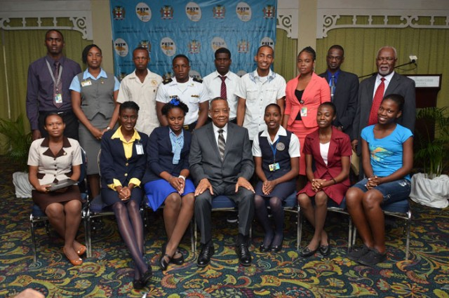 Minister of Labour and Social Security, Hon. Derrick Kellier (seated centre), is pictured with some of the 1,000 students that will benefit from the Programme of Advancement Through Health and Education (PATH) Tertiary Bursary intervention for fiscal year 2013/2014. The Minister, November 13, signed Memoranda of Understanding (MoUs) with representatives of the 18 institutions, through which the bursaries will be offered, during a ceremony at the Knutsford Court hotel in New Kingston. Director of Social Security in the Ministry, Denzil Thorpe (standing 2nd right), and Permanent Secretary in the Ministry, Alvin McIntosh (standing at right), also shared in the moment.