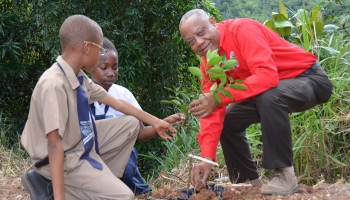 Minister of Agriculture and Fisheries, Hon. Derrick Kellier, and students, Amir Nelson (left) and Alison Johnson (centre) plant an orange tree at the  Orange Hill Primary School, on February 5.  Mr. Kellier launched a tree planting project at the school.