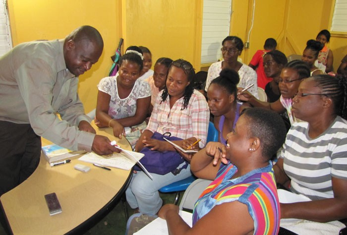 Teacher at the Kitson Town Seventh Day Adventist Evening Institute, in St. Catherine, Wycliffe Brown (left), conducts a session with his students.
