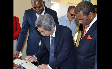 Japanese Ambassador to Jamaica, His Excellency Masanori Nakano (2nd left), signs the visitors' book at the Alexandria Branch Library which was officially opened on June 22. The library was constructed with funds from Japan's Grant Assistance for Grassroots Human Security Project. Member of Parliament for St Ann South West, Zavia Mayne (left) and President of the Northern Caribbean University, Dr Trevor Gardner (right), share the moment.