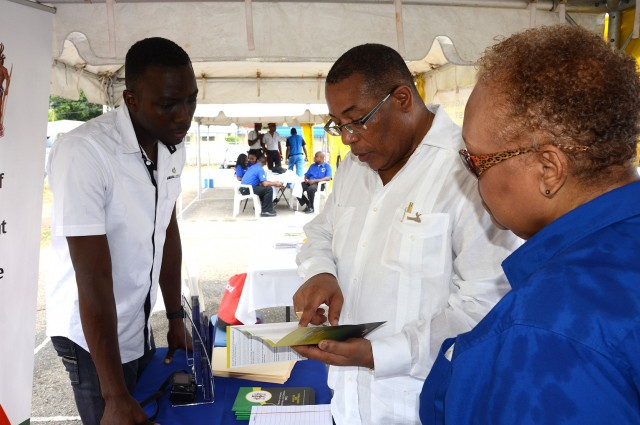 Minister of Industry, Investment and Commerce, Hon. Anthony Hylton (2nd right), discusses a point of interest in a pamphlet on the Jamaica Logistics Hub Initiative  with Project Assistant, Nicolas Spence; and Chief Executive Officer, Jamaica Business Development Corporation (JBDC), Valerie Veira. The Minister was visiting the various booths mounted at the Duhaney Park Community Centre in St. Andrew during a Mobile Business Clinic Initiative (MBCI) event hosted by the JBDC on August 18.