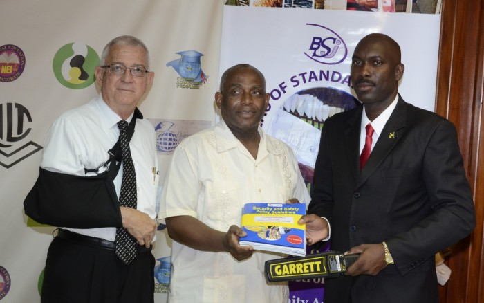 Minister of Education, Hon. Rev. Ronald Thwaites (left) and Director of Safety and Security in the Ministry, Sergeant Coolridge Minto (right), hand over a metal detector and a compilation of revised Safety and Security manuals to Principal of the Haile Selassie High School, Mr. Lorenzo Ellis, during a handing over ceremony at the Ministry's head office on Tuesday, September 29. The Ministry will also be distributing 135 metal detectors to secondary schools this week.