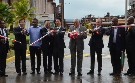 Minister of Transport and Mining, Hon. Mike Henry (4th right), cuts ribbon to officially reopen the Alpart refinery in Nain, St. Elizabeth, on November 24. Assisting are officials of new owners Jiquan Iron and Steel of China and the previous operators UC Rusal of Russia. At third left is former Minister of Mining, Mr. Phillip Paulwell.