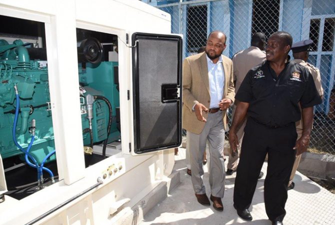Minister of National Security, Hon. Robert Montague (right), and Mayor of St. Ann's Bay, His Worship Michael Belnavis, look at the new standby generator installed at the Ocho Rios Police Station in St. Ann. The Minister officially handed over the equipment on August 31.
