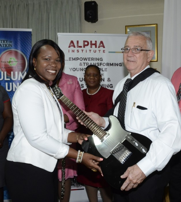 1)	Principal of Denbigh High School, Mrs. Kasan Troupe, is presented with a bass guitar by Education Minister, Hon. Rev. Ronald Thwaites, at the launch of the Music in Schools Programme and handing over of instruments, at the Alpha Institute, South Camp Road, in Kingston, on September 29.