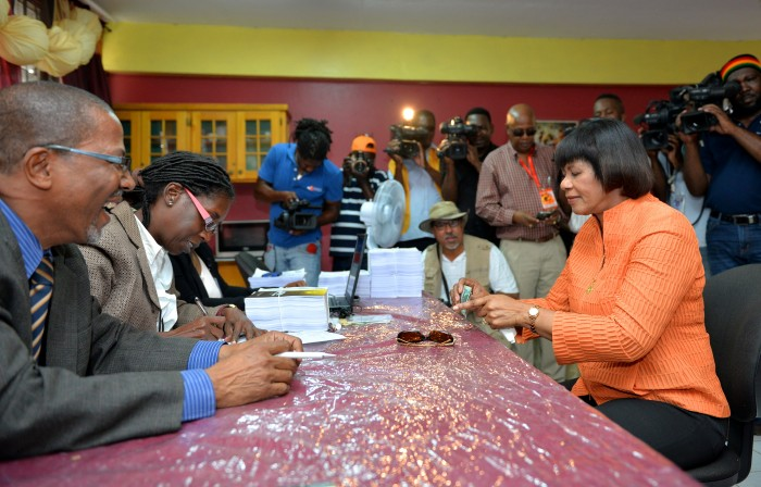 Prime Minister the Most Hon. Portia Simpson Miller (seated, right), counts her $3,000 which she is about to hand over as her nomination fee as a candidate for the constituency of South Western St. Andrew in the February 25 general election, at the Greenwich Town All Age School in Kingston, today (February 9).