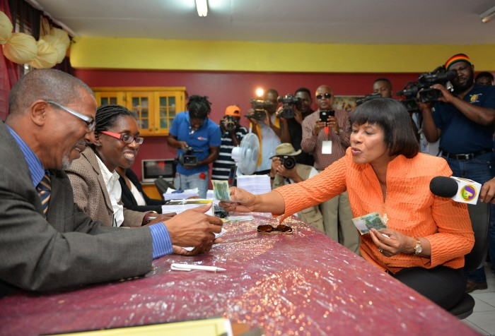 Prime Minister the Most Hon. Portia Simpson Miller (seated, right), pays over her nomination fee of $3,000 as a candidate for the constituency of South Western St. Andrew in the February 25 general election, at the Greenwich Town All Age School in Kingston, today (February 9).
