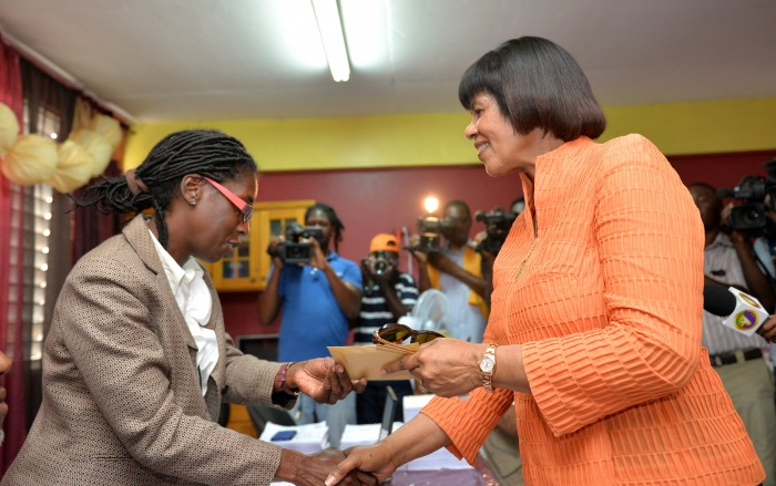 Prime Minister the Most Hon. Portia Simpson Miller (right), accepts her receipt and nomination paper from a representative of the Electoral Office of Jamaica (EOJ), after she completed the process, today (February 9), at the Greenwich All Age School, in South West St. Andrew. Mrs. Simpson Miller was nominated as the candidate for the constituency in the general election, to be held on Thursday, February 25, 2016.