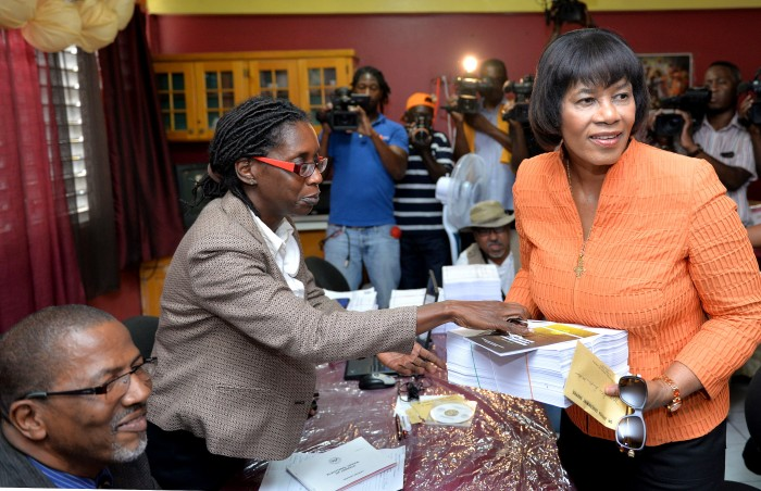 Prime Minister the Most Hon. Portia Simpson Miller (right), accepts her nomination paper and copies of the voters' list from a representative of the Electoral Office of Jamaica (EOJ), after completing the process, today (February 9), at the Greenwich All Age School, in South West St. Andrew. Mrs. Simpson Miller was nominated as the candidate for the constituency in the general election, to be held on Thursday, February 25, 2016.