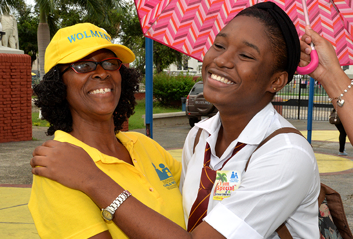Chair of the National Child Month Committee (NCMC), Dr. Pauline Mullings (left), hugs lower-sixth-form student of the Wolmer's Girls' School, Shakeema Evans, during the National Child Month Committee's (NCMC) annual Children's Day activity held on May 19 at St. William Grant Park, downtown Kingston.