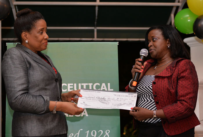 Executive Director of the National Road Safety Council (NRSC), Mrs. Paula Fletcher (left), accepts a donation of $350, 000 in aid of road crash victims from First Vice President of the Pharmaceutical Society of Jamaica (PSJ), Dr. Ernestine Watson, at the PSJ Induction and Awards Ceremony, held on  November 18 at the Hotel Four Seasons, in Kingston.
