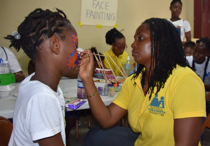 National Child Month Committee (NCMC) member, Nicole Patrick Shaw, paints the face of a little girl at the Children's Health and Wellness Fair staged by the NCMC on May 28 at the Douglas Orane Auditorium, Wolmer's Boys School, Kingston.