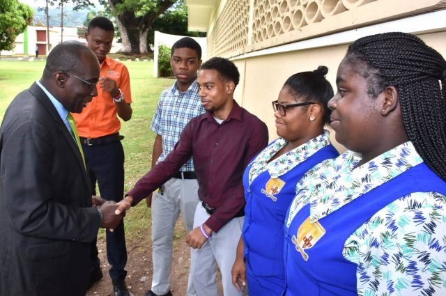 Education, Youth and Information Minister, Senator the Hon. Ruel Reid (left), is greeted by foreign language trainee teacher, Ryan Mullings, on arrival at Shortwood Teachers' College in St. Andrew on Friday (October 27) for the Ministry's ninth foreign languages annual general meeting. Others (from second left) are trainee teachers, Shamore Roberts, Justin Kerr, Tanra Wright and Desirée Walker.