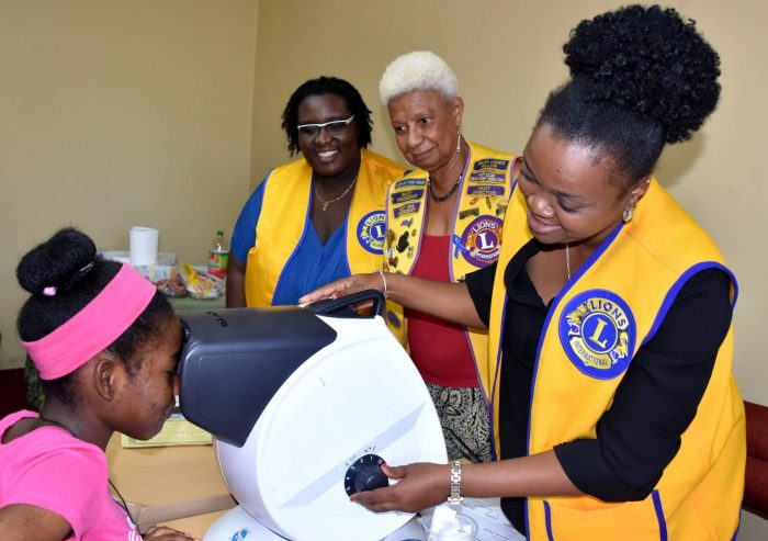 Rushelle Clarke-Lindsay (right) of the Lions Club of St. Andrew Central performs an eye analysis on 15-year old Zariah Christie (left) of the Mona High School in St. Andrew. The occasion was the Children's Health and Wellness Fair staged by the National Child Month Committee (NCMC) on May 28 at the Douglas Orane Auditorium, Wolmer's Boys School, Kingston Looking on (from 2nd left) are: President-elect of the Lions Club of St. Andrew Central, Theresa Bowen; and Chairman of the Club's Health Committee, Brenda Miller.