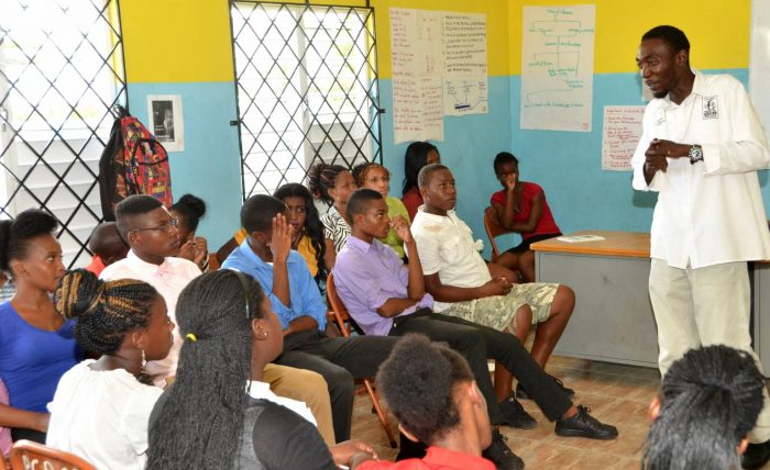 Member of the Citizen Security and Justice Programme (CSJP) Men with a Message advocacy group, Jermaine Austin, addresses young people who benefitted from a CSJP summer school workshop in 2015.