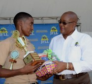 Winner of the Jamaican Foundation for Lifelong Learning's (JFLL) poster competition, Allan Morrison (left) accepts his prize from Board Chairman of the JFLL, Audrey Hinchcliffe. The presentation was made during the staging of the JFLL's 'Opportunities Fair', at Emancipation Park in Kingston on July 23.