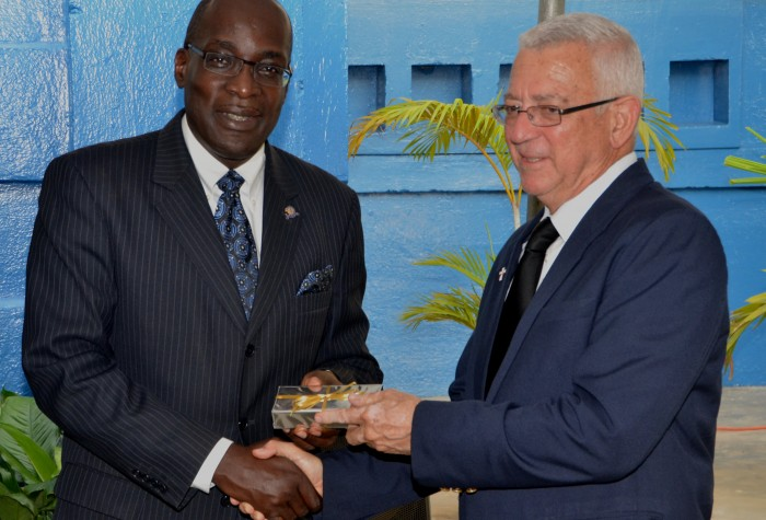 Minister of Education, Rev. Hon. Ronald Thwaites (right) accepts a token from Principal, Jamaica College, Senator Ruel Reid during the official opening of the institution's state-of-the-art museum on August  28, at its Old Hope Road grounds in St. Andrew.