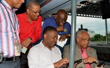 Science, Technology, Energy and Mining Minister, Hon. Phillip Paulwell (left, seated); and Transport, Works and Housing Minister, Dr. the Hon. Omar Davies (right, seated), peruse their mobile devices after accessing the Jamaica Urban Transit Company's (JUTC) Wi-Fi Internet service on one of the state entity's buses, during Friday's (February 12) launch of the Wi-Fi Systems Pilot Project, at the Half Way Tree Transport Centre in St. Andrew. Looking on, from left, are: Manager, Information Technology, JUTC, Brian Tulloch; Chief Executive Officer, Universal Service Fund (USF), Hugh Cross; and JUTC Managing Director, Colin Campbell.