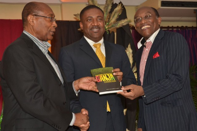Minister of Science, Technology, Energy and Mining, Hon. Phillip Paulwell (centre),  is presented with a copy of the book - 'Cannabis, Marijuana, Ganja: the Jamaican Global Connection'- by Authors, Dr. Henry Lowe (left) and Professor Errol Morrison, during a  launching ceremony,  at the Eden Gardens in Kingston, on December 10.