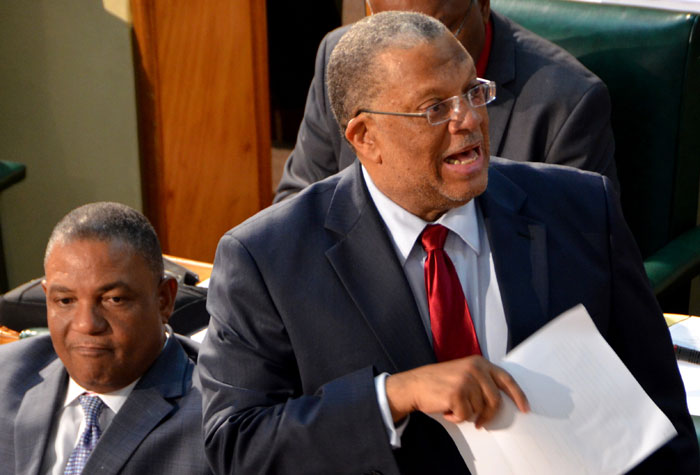Minister of Finance and Planning, Dr. the Hon Peter Phillips (right), opening the 2014/15 Budget Debate in the House of Representatives on Thursday, April 17. Listening at left  Minister with responsibility for the Public Service,  Hon. Horace Dalley.