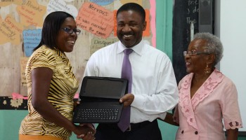 Minister of Science, Technology, Energy and Mining, Hon. Phillip Paulwell (centre), presents Vice Principal and Grade six teacher at Clan Carthy Primary School, Winsome Reid, with one of the 30 tablet computers, which were handed over to the school by Geo TechVision Enterprises today (July 28), under the Government's Tablets in Schools initiative. Chairman of eLearning Jamaica, Yvonne McCalla Sobers (right) also participated in the presentation ceremony.