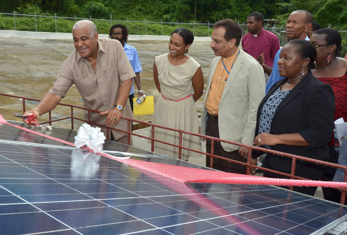 Minister of Water, Land, Environment and Climate Change, Hon. Robert Pickersgill (left), cuts the ribbon to a solar power system, to be used for operating the Pleasant Valley water catchment facility, in Clarendon, recently. Others sharing in the occasion are (from second left): Programme Manager for the Environmental Foundation of Jamaica, Allison Rangolan-McFarlane; Resident Representative for the United Nations Development Programme (UNDP), Dr. Arun Kashyap; and National Coordinator for the Global Environment Facility Small Grants Programme (GEF SGP), Hyacinth Douglas.