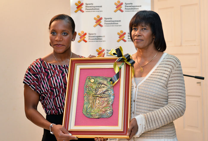 Prime Minister, the Most Hon. Portia Simpson Miller presents a gift to World 100-metre breaststroke Champion, Alia Atkinson at a reception held at Vale Royal on Wednesday, January 14.